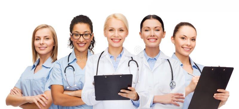 Doctores y enfermeras de sexo femenino sonrientes con el estetoscopio imagen de archivo