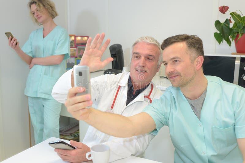 Doctores y enfermeras sonrientes del equipo en el hospital que toma el selfie imagenes de archivo