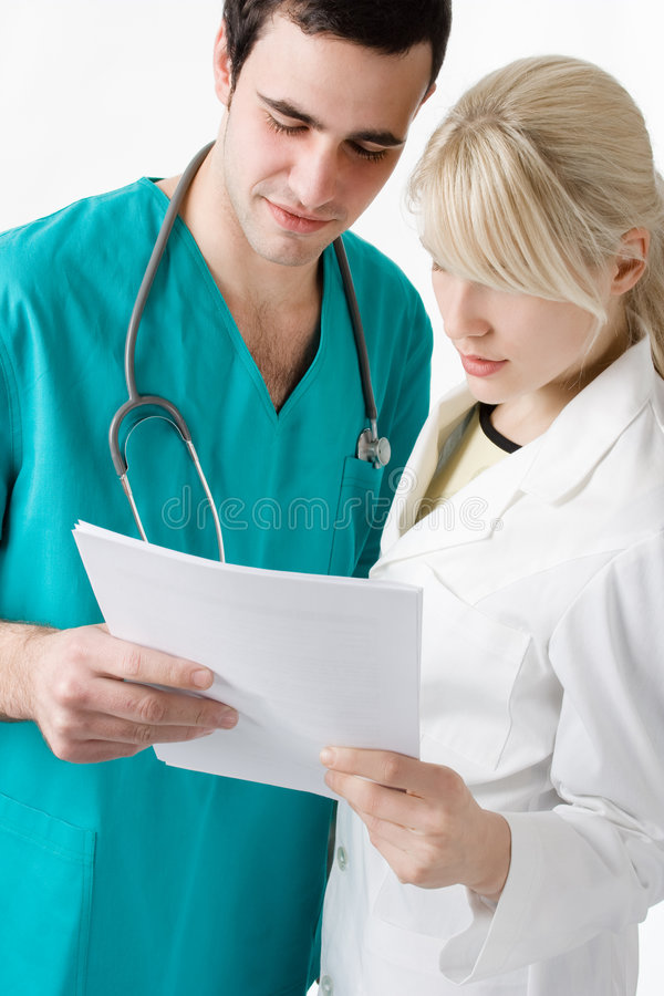 Doctors. Two young doctors reading results stock image