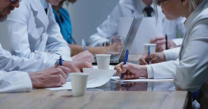 Doctors analyzing cervical spine x-ray. Medium shot of doctors analyzing cervical spine x-ray during a meeting royalty free stock image