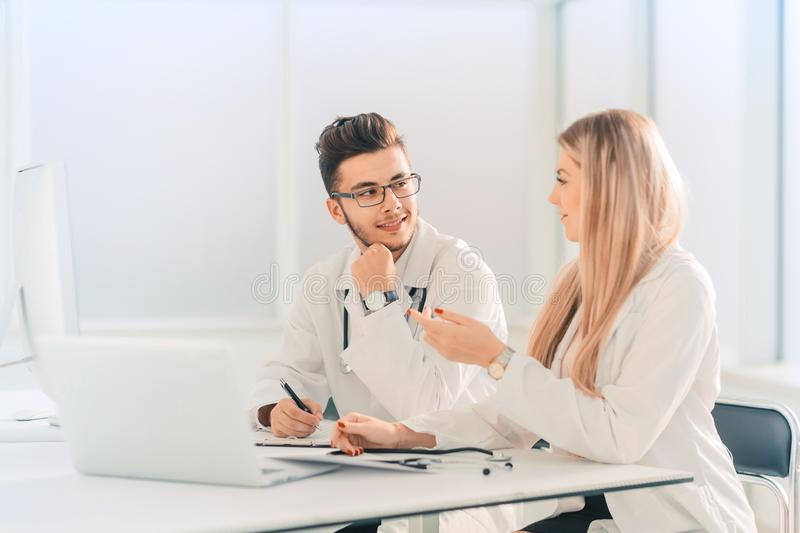 Doctors colleagues talking sitting at a table in the office royalty free stock image