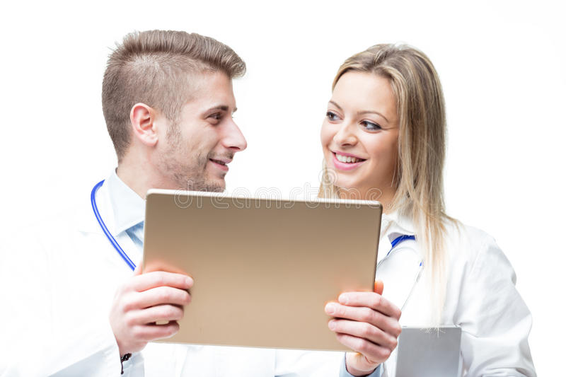 Doctors discussing about exam`s data with a tablet stock image