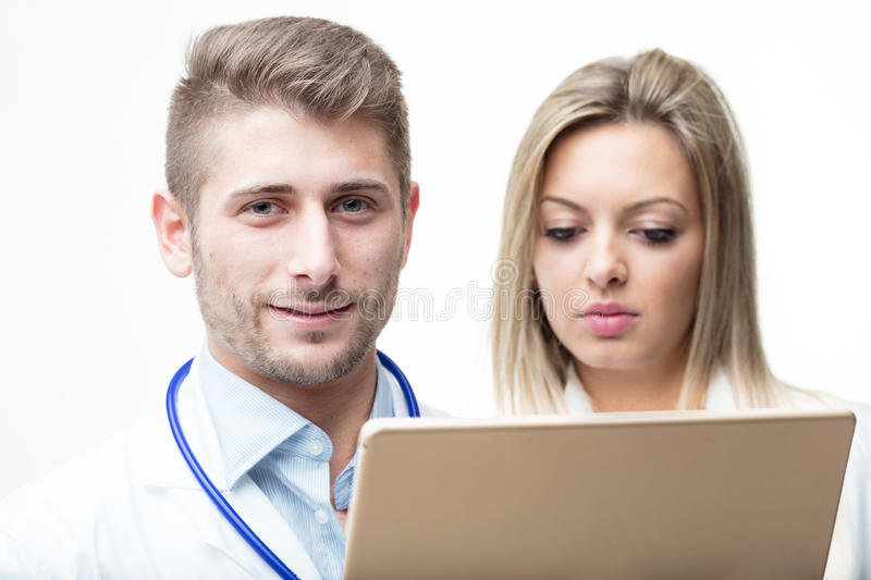 Doctors discussing about exam`s data with a tablet royalty free stock photography