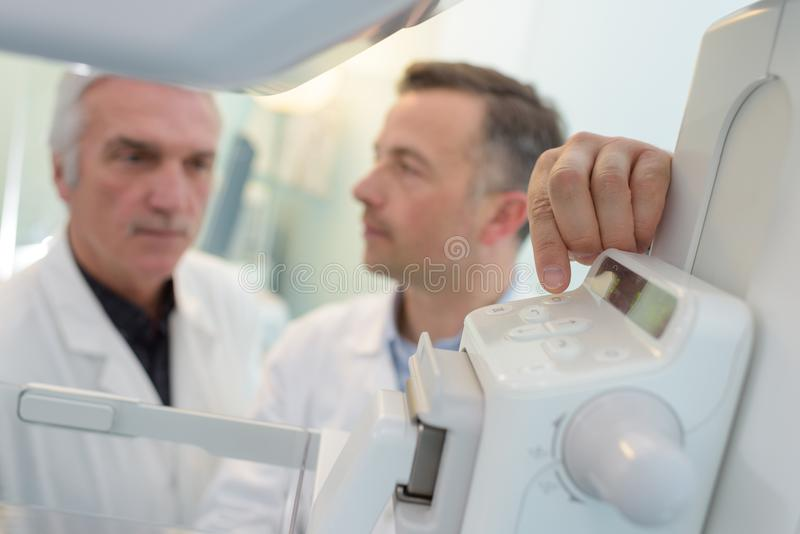 Doctors discussing next to mri machine in hospital stock photography