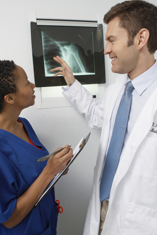 Doctors Discussing X-Ray Report. Side view of two multiethnic doctors discussing X ray report stock image