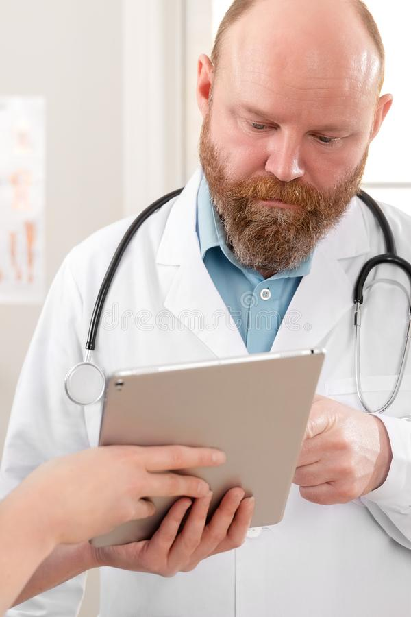 Doctors discussing report about a patient at tablet computer in hospital stock photography
