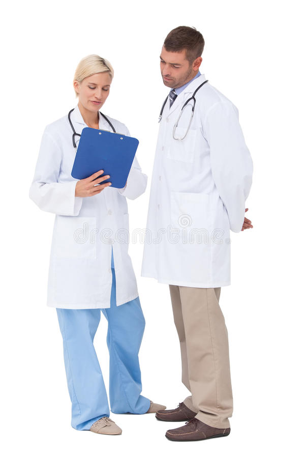 Doctors discussing something on clipboard royalty free stock images