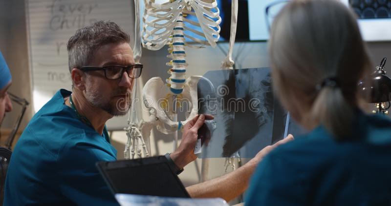Doctors examining cervical spine x-ray. Medium shot of doctors examining cervical spine x-ray image royalty free stock images