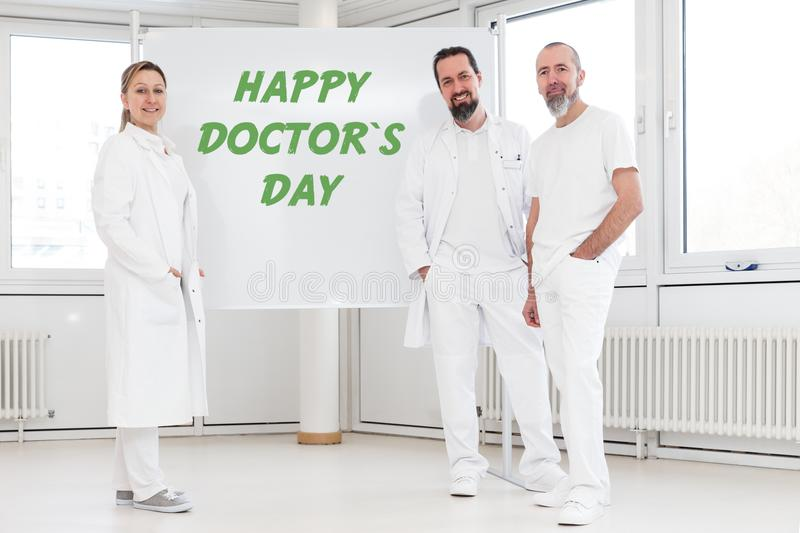 Doctors in front of a whiteboard with the text happy doctor`s da. Medicine staff in front of a whiteboard with the text happy doctor`s day royalty free stock photo
