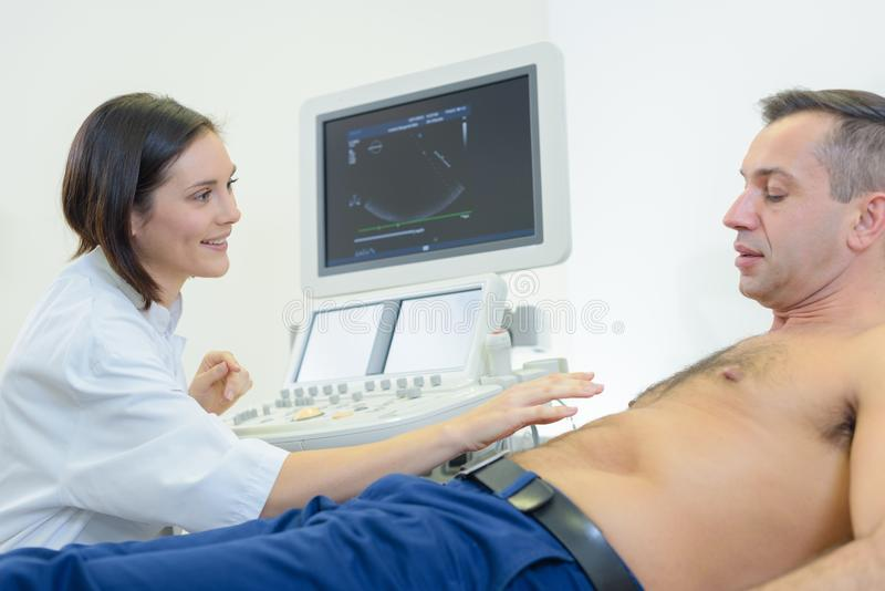 Doctors holding probe while performing abdominal ultrasound exam. Doctors is holding a probe while performing abdominal ultrasound exam stock photos