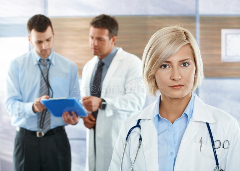 Doctors on hospital corridor. Healthcare workers on hospital corridor female doctor in front looking at camera royalty free stock photo