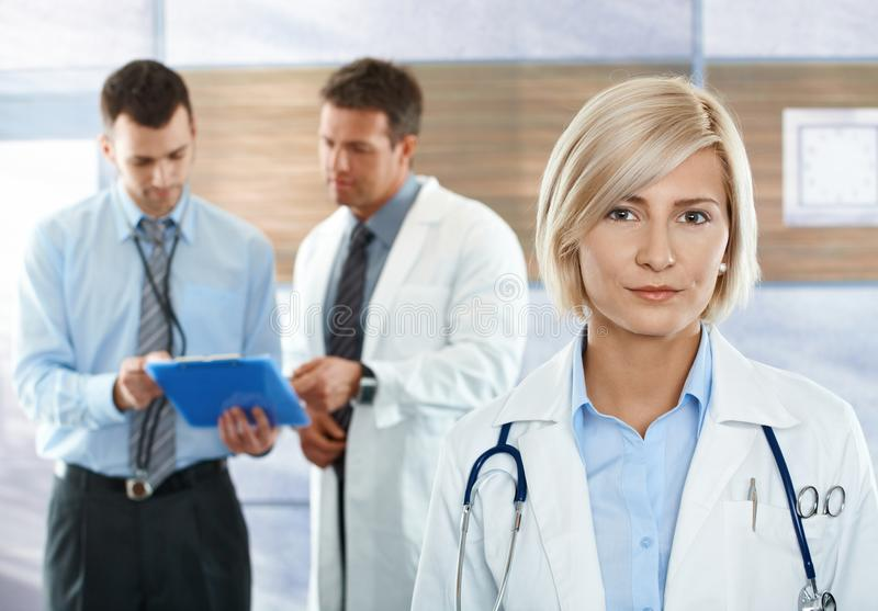 Doctors on hospital corridor. Medical team on hospital corridor female doctor in front looking at camera, smiling royalty free stock images
