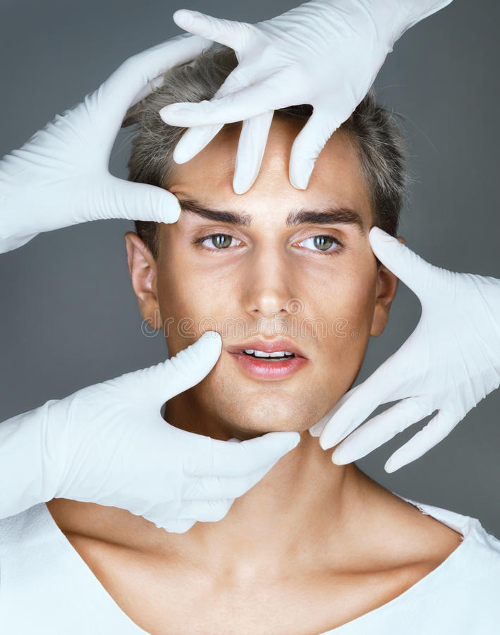 Doctors are investigating the young man's face in front of a beauty treatment stock photography