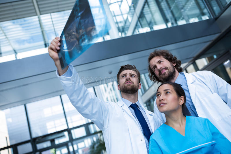 Doctors and nurse examining X-ray report. In hospital stock photos
