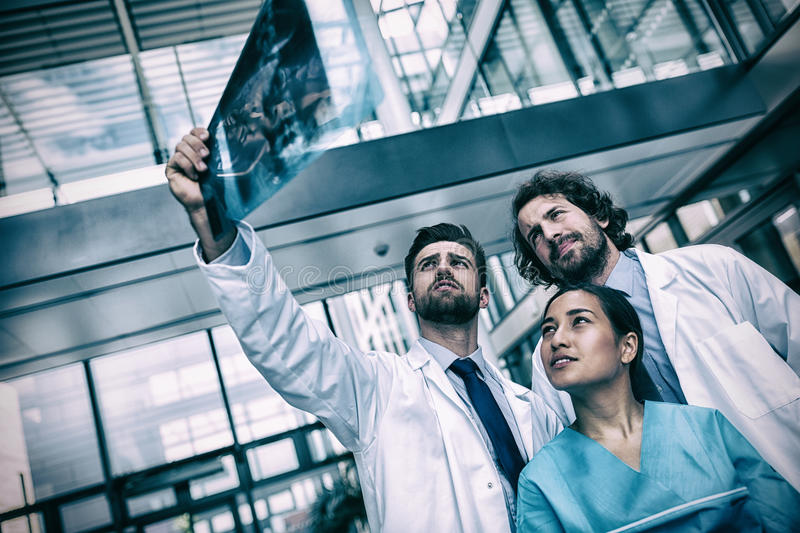 Doctors and nurse examining X-ray report. In hospital stock images