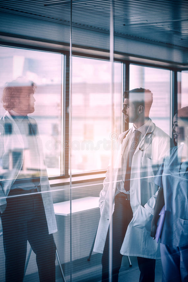 Doctors and nurse having conversation in corridor stock images