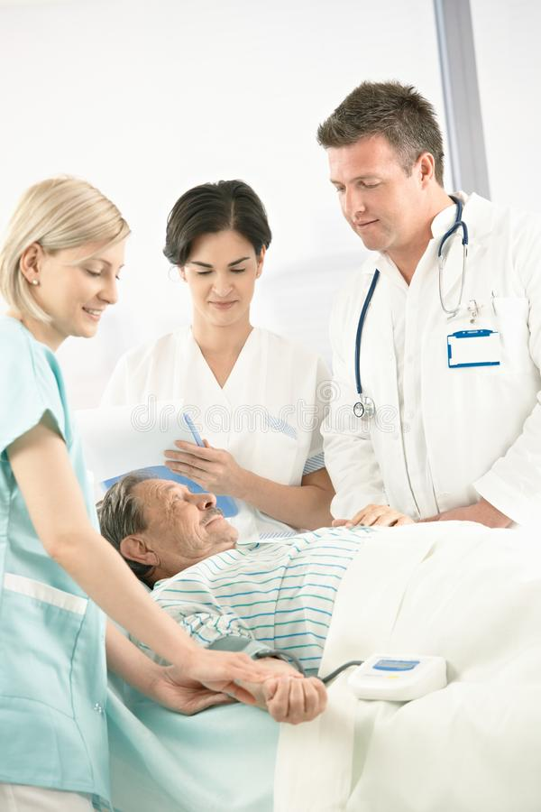 Doctors and nurse with older patient royalty free stock photography