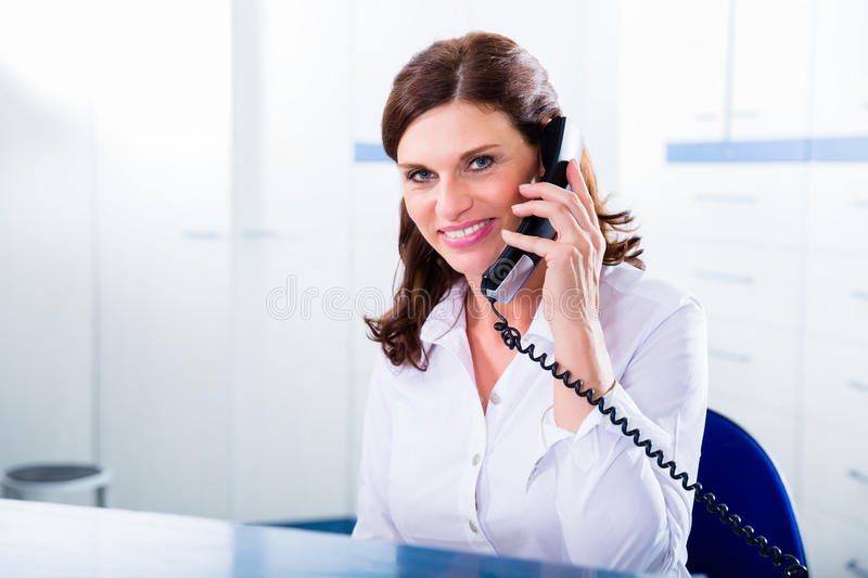 Doctors nurse with telephone in front desk royalty free stock photos