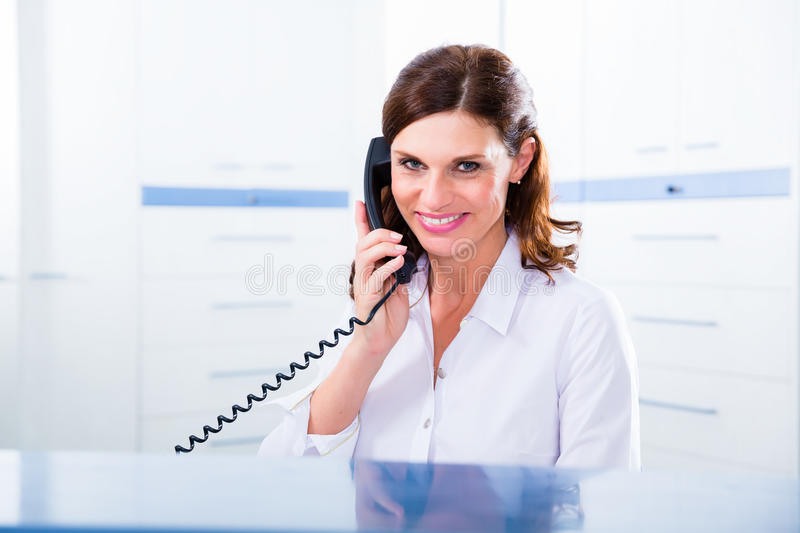 Doctors nurse with telephone in front desk royalty free stock images