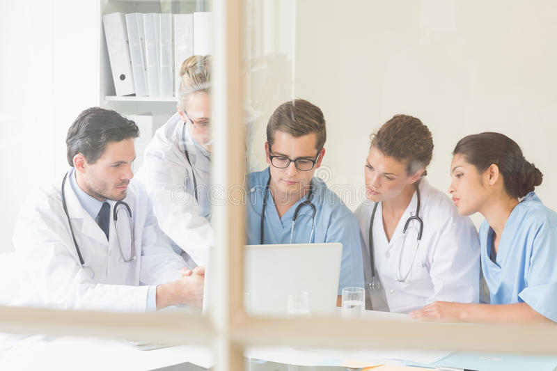 Doctors and nurses discussing over laptop royalty free stock photo