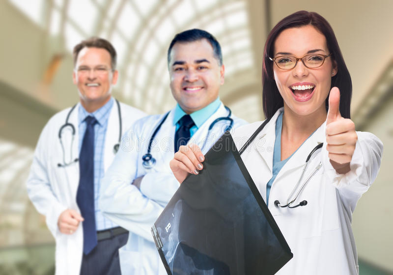 Doctors or Nurses Holding X-ray Inside Hospital. Doctors or Nurses With Thumbs Up Holding X-ray Standing Inside Hospital stock photos