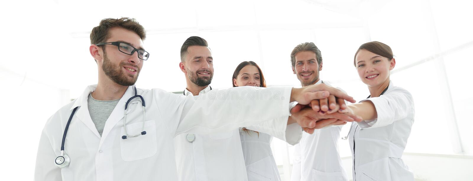 Doctors and nurses in a medical team stacking hands royalty free stock photo