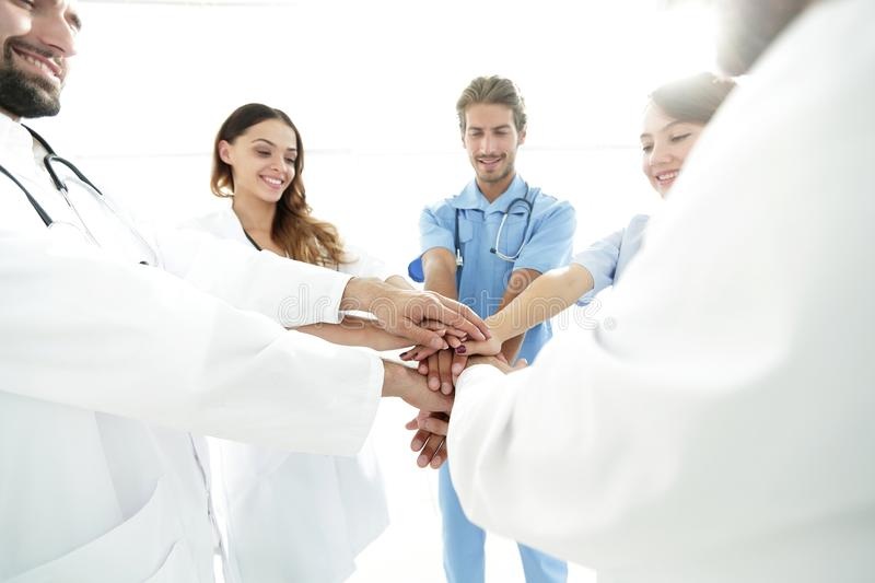 Doctors and nurses in a medical team stacking hands. Concept of unity stock photography