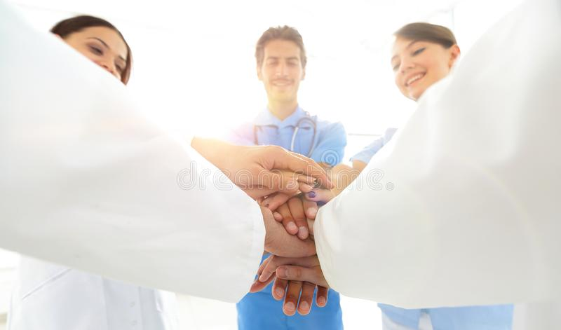 Doctors and nurses in a medical team stacking hands. Concept of unity royalty free stock image