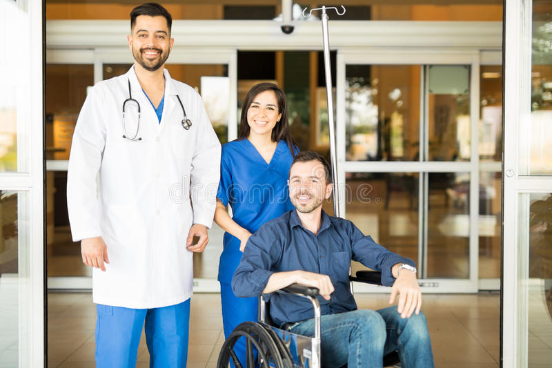 Doctors and patient in hospital entrance. Couple of doctors and a patient in a wheelchair standing in the hospital entrance and smiling stock photos