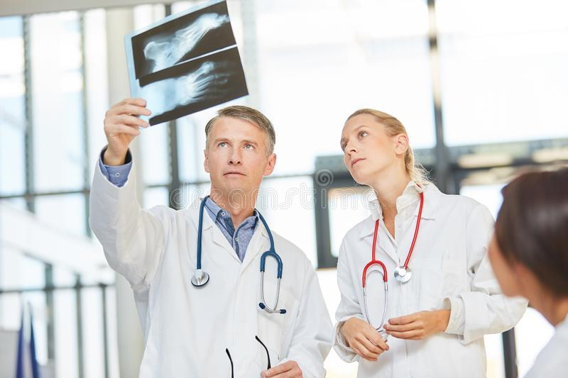 Doctors with radiograph in radiology. Doctors with X-ray image in the evaluation in a workshop in radiology royalty free stock image