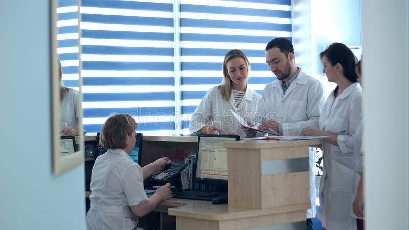 Doctors reviewing patient folders at hospital reception desk royalty free stock images