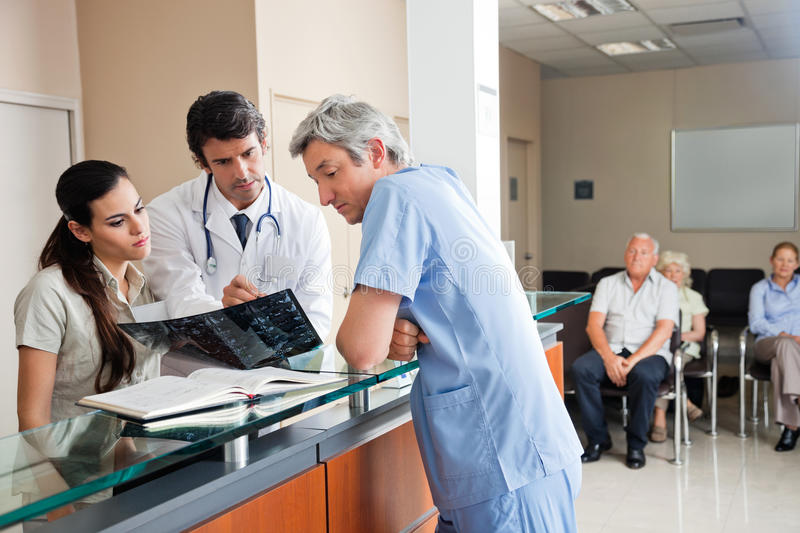 Doctors Reviewing X-ray At Reception. Doctors reviewing x-ray at hospital reception while people sitting in background stock photo