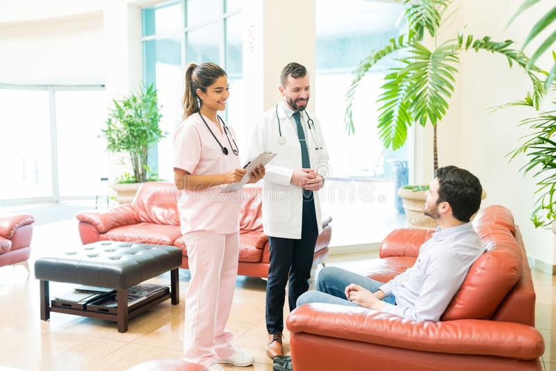 Doctors Speaking To Man In Waiting Room At Hospital royalty free stock images