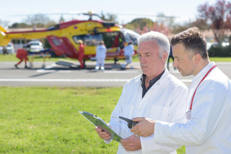Doctors standing by helicopter checking patients record royalty free stock photos
