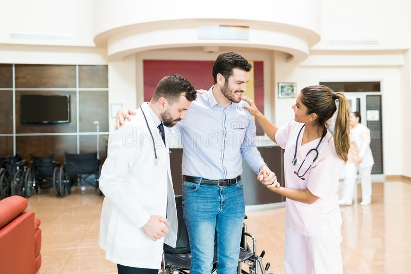 Doctors Supporting Man To Stand While Saying Goodbye At Hospital stock photos