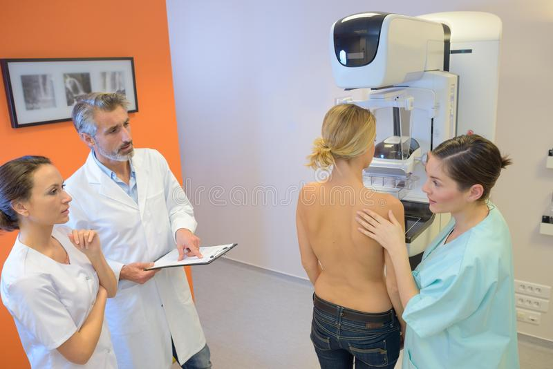 Doctors talk as patient takes breast cancer screening. Breast royalty free stock image