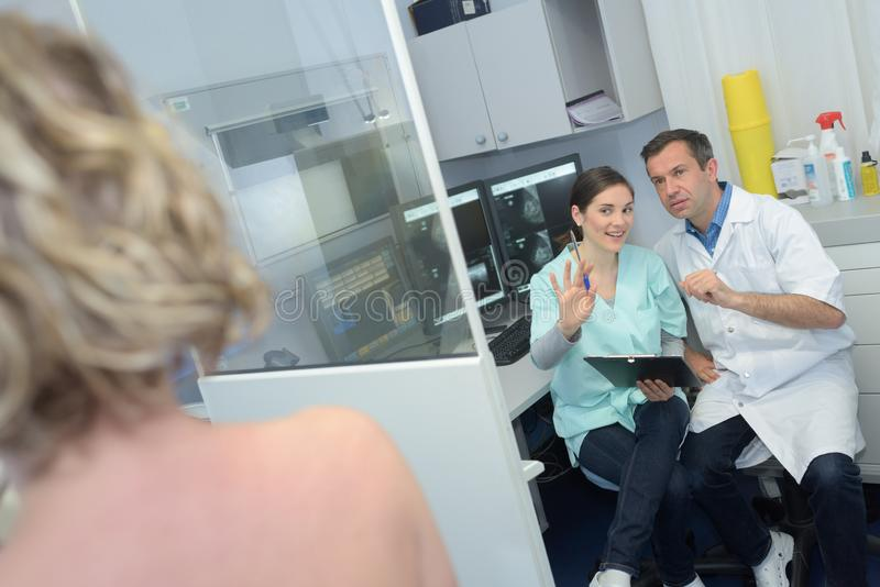 Doctors telling patient not to move during examination. Doctors stock photos