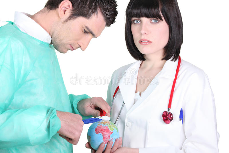 Doctors treating a mini globe royalty free stock photos