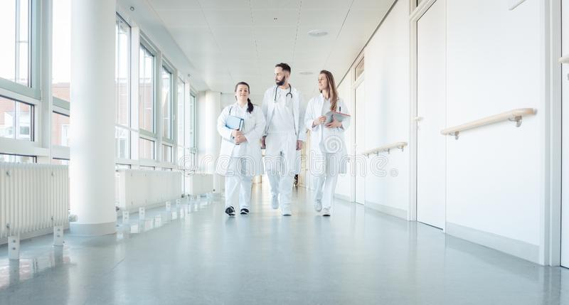 Doctors, two women and a man, in hospital stock images
