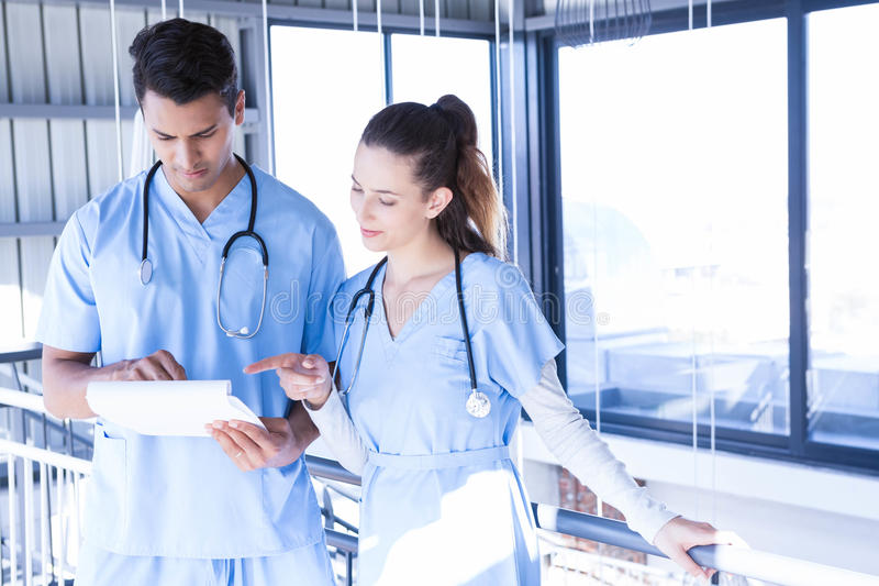 Doctors using digital tablet in corridor royalty free stock photography