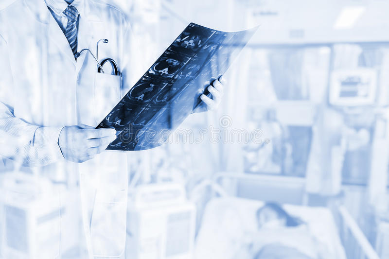 Doctors viewing film X-ray of the patient with blurred patient in hospital room ,Concept medicine background stock photography