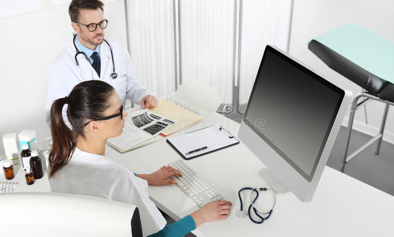 Doctors working at desk in medical office with computer. Drugs and documents stock photography