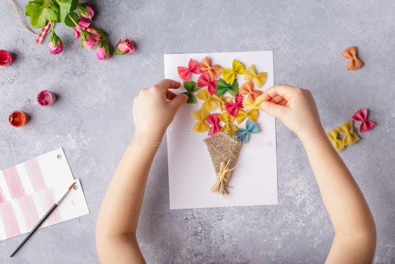 Document ambachten voor moederdag, 8 maart of verjaardag Klein kind die een boeket van bloemen doen uit gekleurd document en gekl stock foto