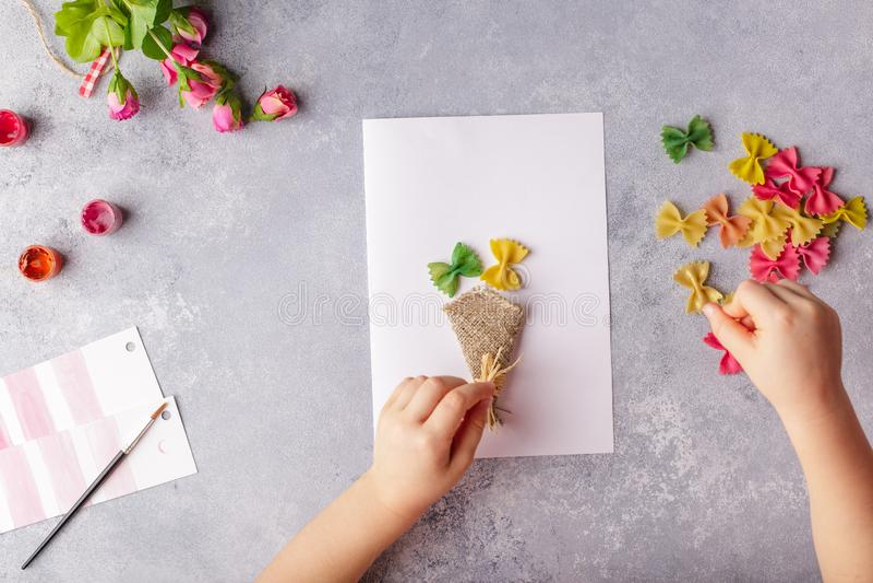 Document ambachten voor moederdag, 8 maart of verjaardag Klein kind die een boeket van bloemen doen uit gekleurd document en gekl stock afbeeldingen
