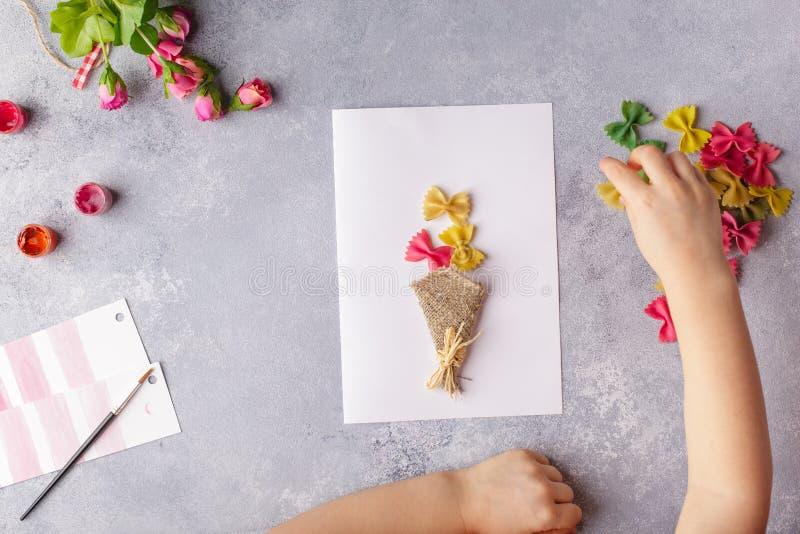Document ambachten voor moederdag, 8 maart of verjaardag Klein kind die een boeket van bloemen doen uit gekleurd document en gekl royalty-vrije stock fotografie