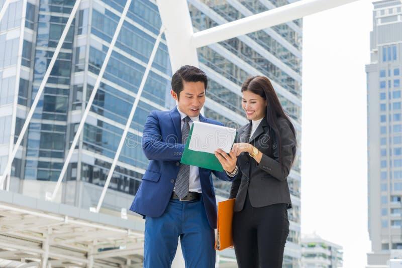 Document asiatique de participation d'homme d'affaires et de femme d'affaires en main et parler du plan d'action photos libres de droits