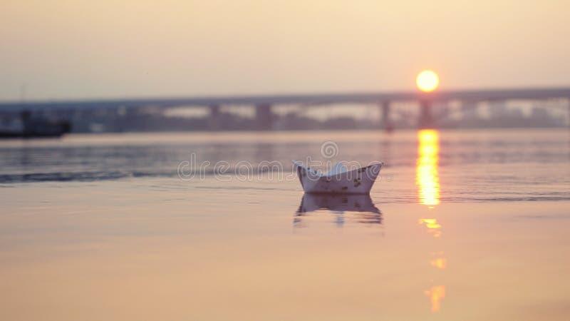 Document boot op het water tijdens mooie zonsondergang met bezinningszon in overzees royalty-vrije stock afbeelding