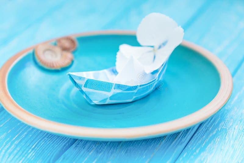 Document boten met bloem in een ceramische kom op een blauwe houten achtergrond De zomer reizend concept Vrije ruimte royalty-vrije stock foto