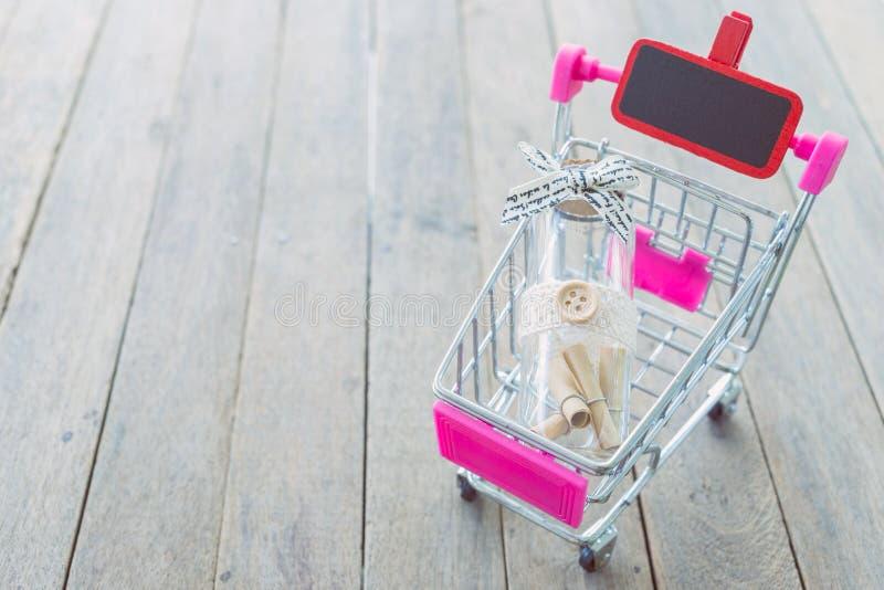 Document broodjes in een fles in een minikar op houten lijst stock fotografie
