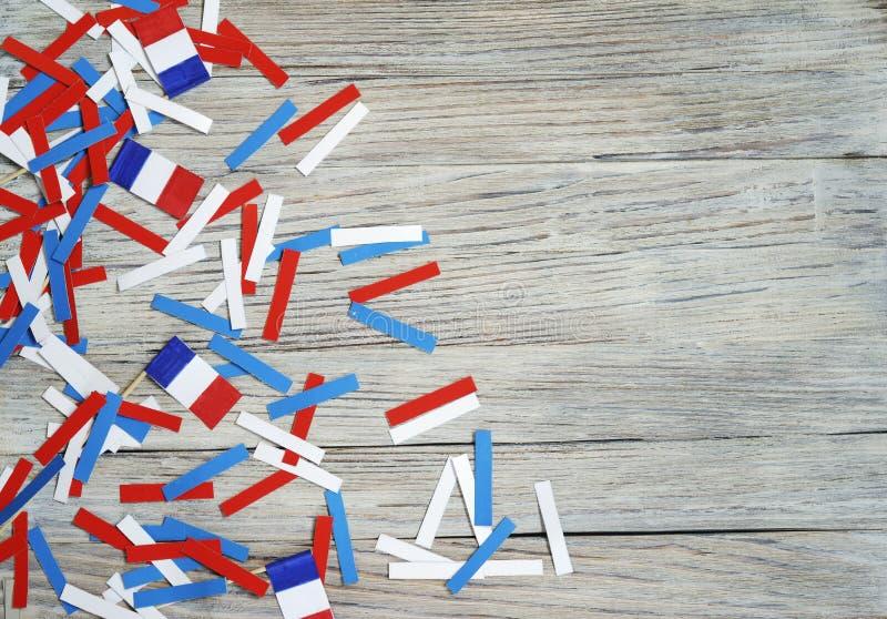 Document confettien van de nationale kleuren van Frankrijk, wit-blauw-rood op een witte houten achtergrond met vlaggen, de dag va royalty-vrije stock afbeeldingen